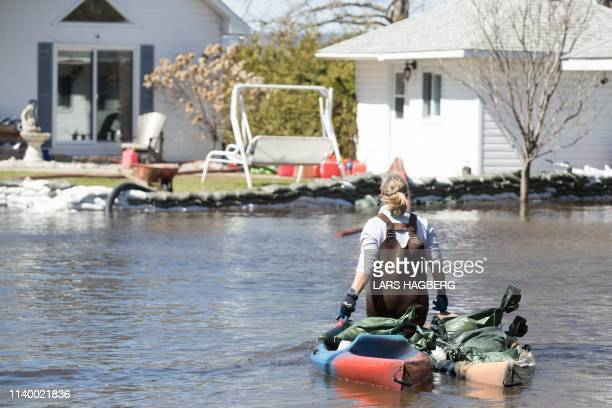 A woman moves sandbags with a kayak near her house in Constance Bay west of Ottawa Ontario on April 28 2019 More than 5000 people were told to...
