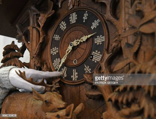 A woman moves the hands of a historic cuckoo clock on March 19 2018 at the German Clock Museum in Furtwangen southern Germany Time in Germany will...