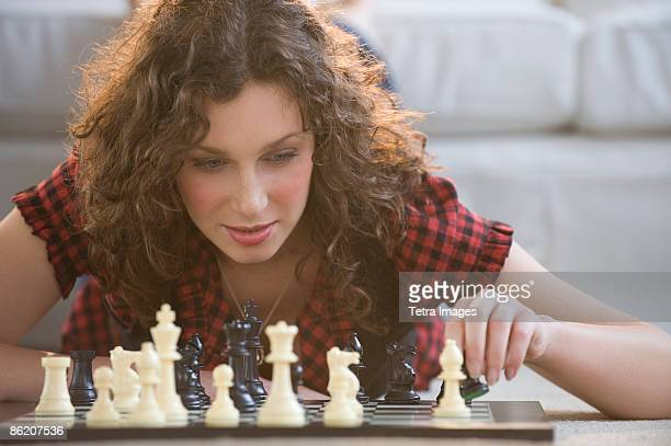 Woman moving chess piece