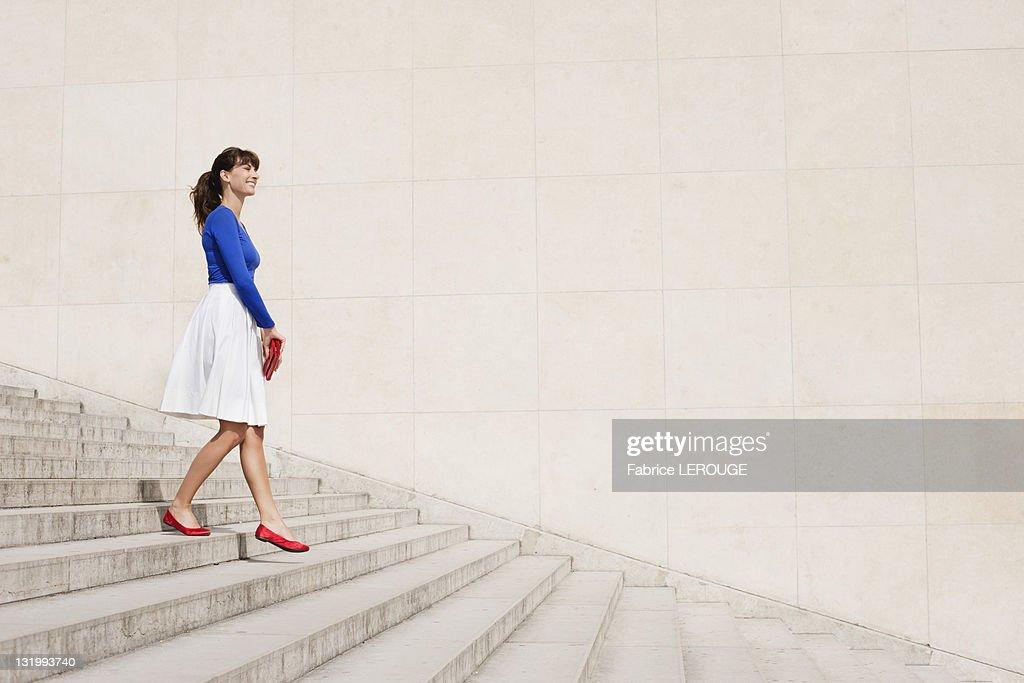 Woman moving down steps, Paris, Ile-de-France, France : Foto de stock