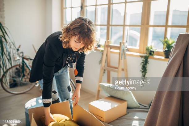 woman moving in into new apartment - packing stock pictures, royalty-free photos & images