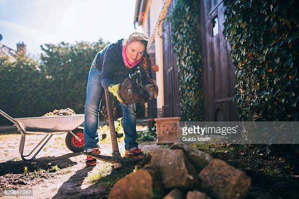 Woman moving rocks in the garden.
