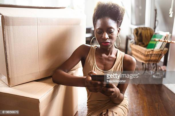 woman moving the house and texting on the phone