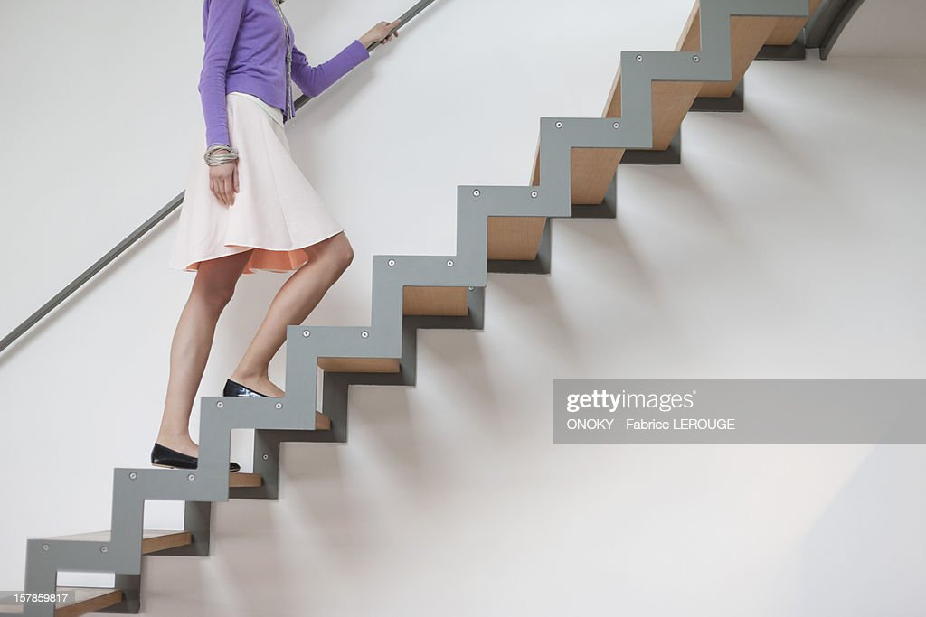 Woman moving up stairs : ストックフォト