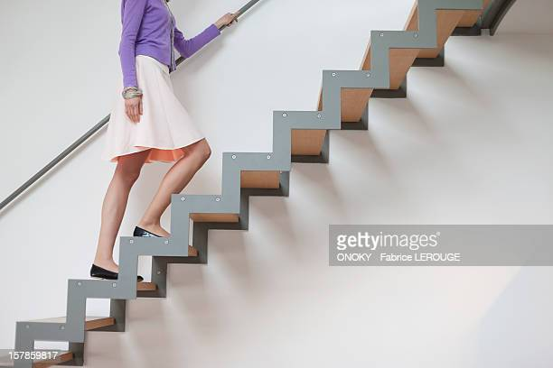 woman moving up stairs - stairs stock photos and pictures