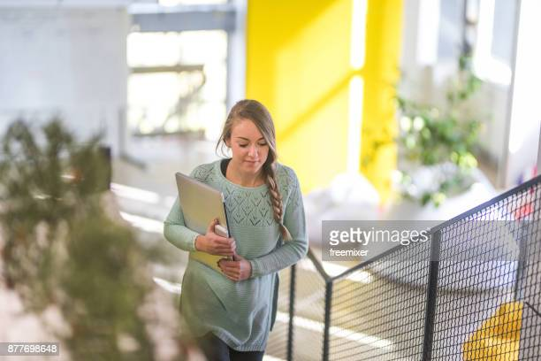Woman moving up the stairs to go to the meeting in the office