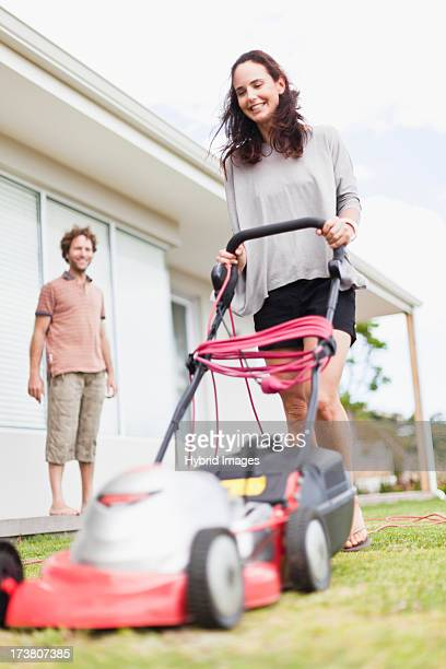 Woman mowing green lawn