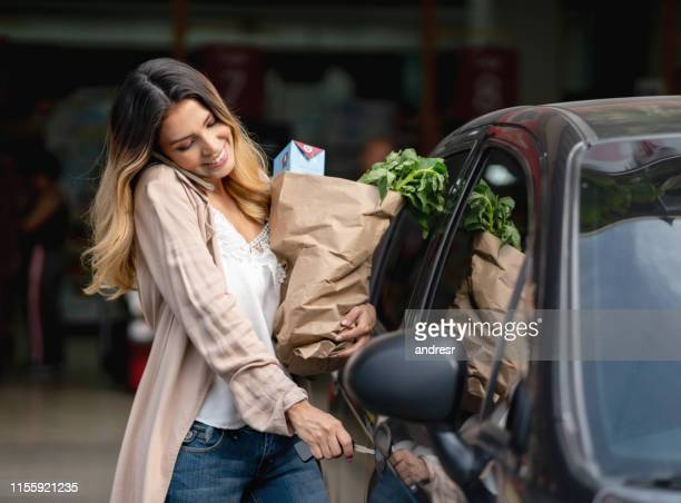donna multitasking salire in macchina dopo aver fatto la spesa al negozio di alimentari - arrivo foto e immagini stock