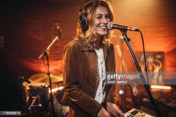 woman musician singing and playing keyboard - electronic music stock pictures, royalty-free photos & images