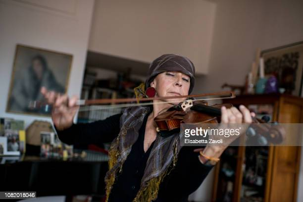 senior woman playing violin in a house - violin stock pictures, royalty-free photos & images