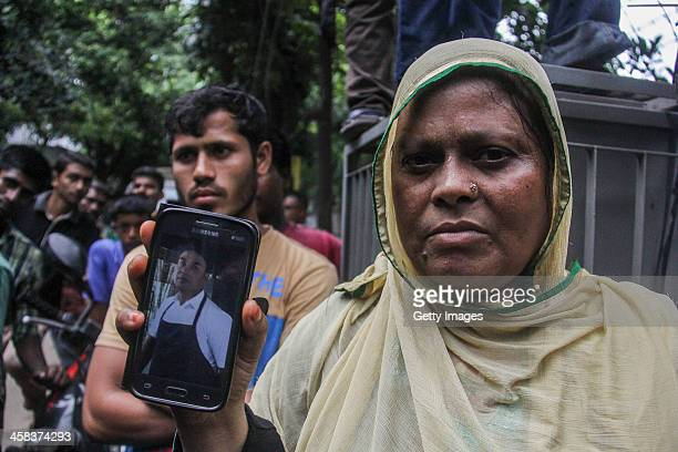 A woman named Johra shows a mobile phone picture of her brother in law Saidul who is an employee of Holey Artisan Bakery cafe which was attacked by...