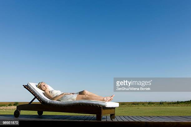 Woman napping on lounge chair on deck