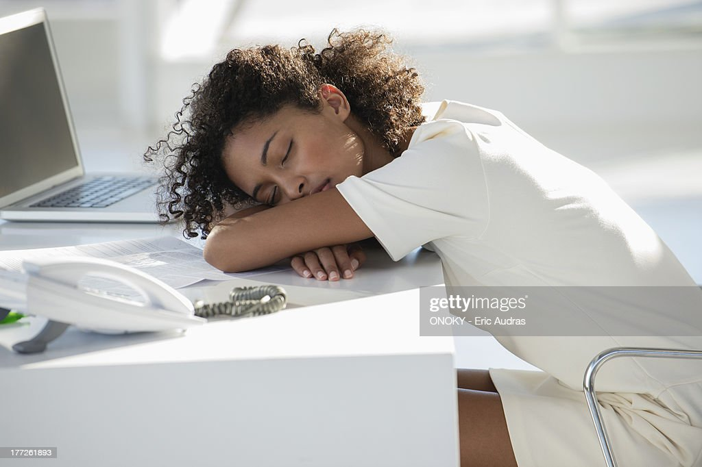 Woman napping with her head resting on desk : Stock Photo