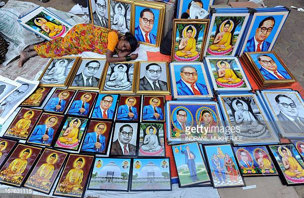A woman naps amidst photo frames with images of the architect of the Indian constitution Bhim Rao Ambedkar and Lord Gautam Buddha on the eve of...