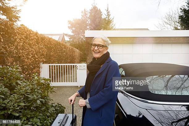 Woman near car on driveway holding suitcase looking at camera smiling