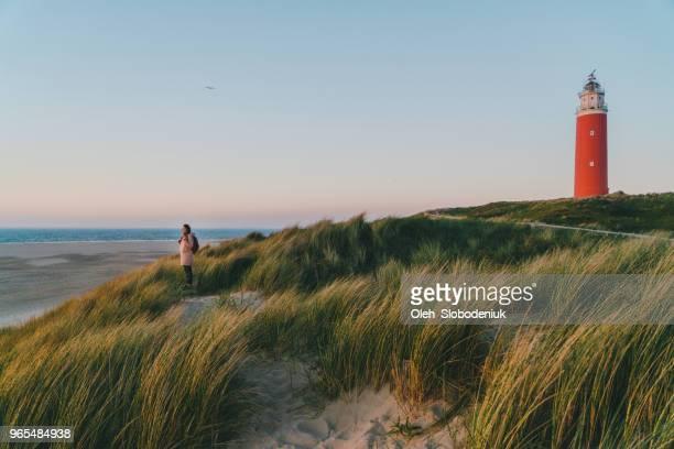 vrouw in de buurt van de vuurtoren op het eiland texel bij zonsondergang - nederlandse cultuur stockfoto's en -beelden