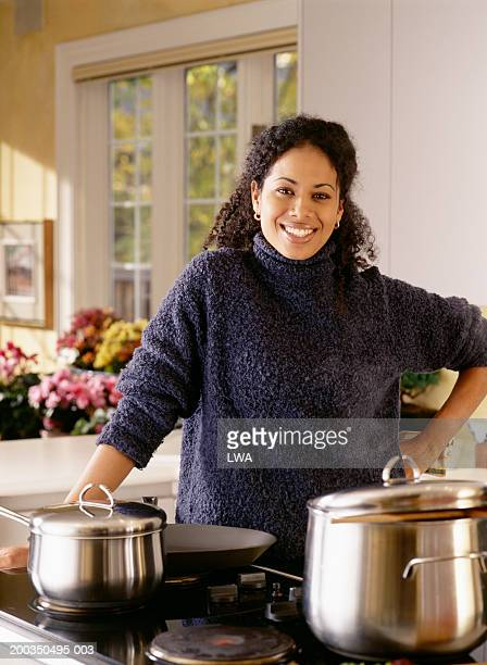 woman near stove in kitchen smiling, portrait - burner stove top stock pictures, royalty-free photos & images