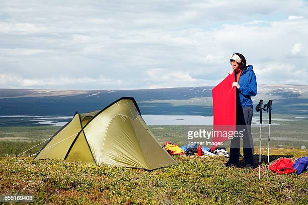 Woman near tent in mountains