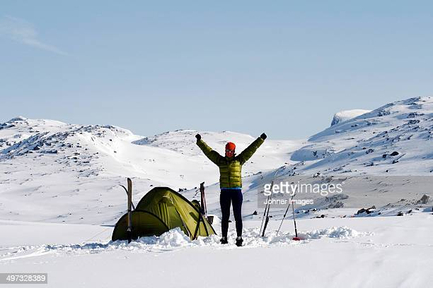 woman near tent in winter mountains, riksgransen, lapland, sweden - swedish lapland stock-fotos und bilder