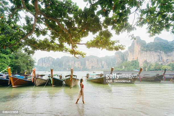 Woman near the boats on beach in Thailand