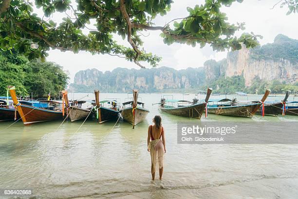 woman near the boats on beach in thailand - thailand stock-fotos und bilder