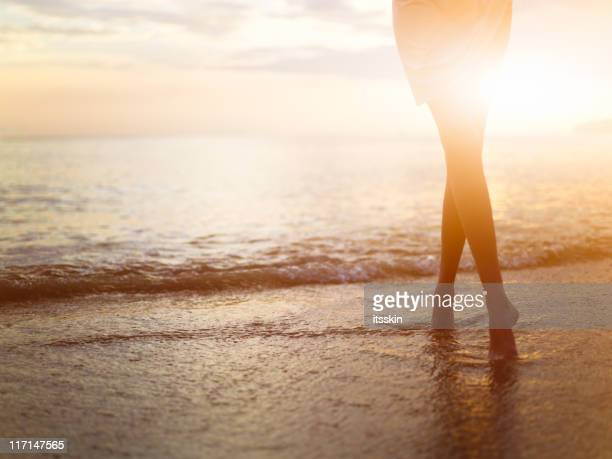 Woman near the ocean. Sunset time.