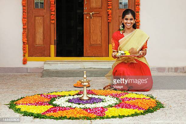 Woman next to a pookalam