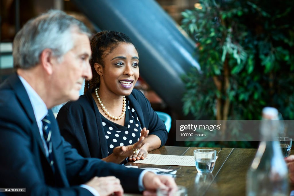 Woman next to male manager in business meeting : Stock Photo