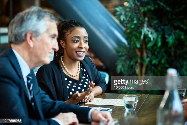 woman next to male manager in business meeting - role model stock pictures, royalty-free photos & images