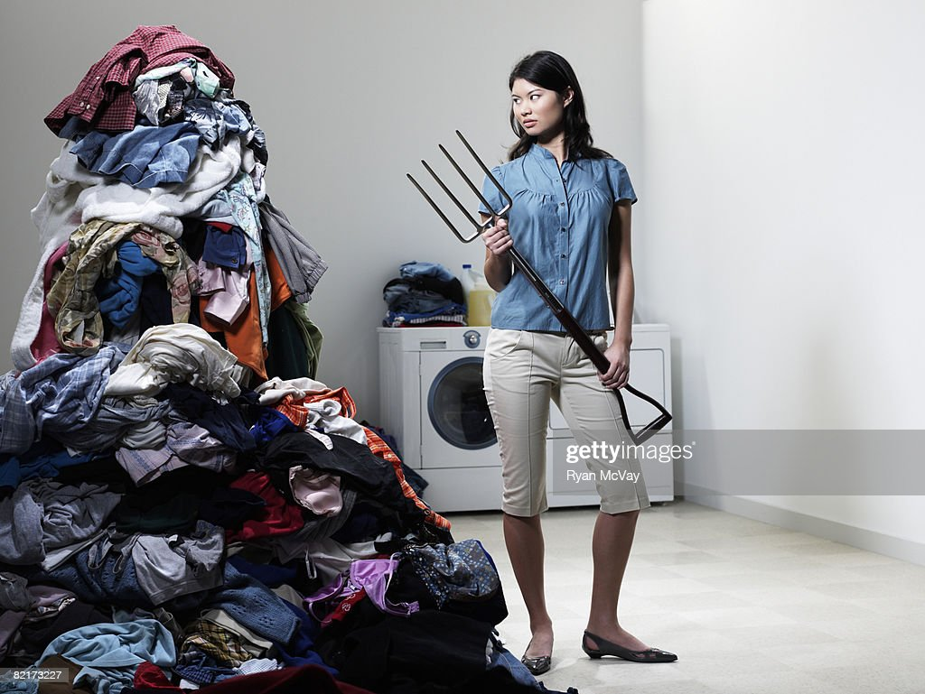 Woman next to pile of Laudry with pitchfork. : Stock Photo
