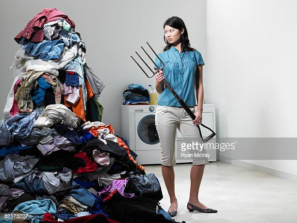 Woman next to pile of Laudry with pitchfork.