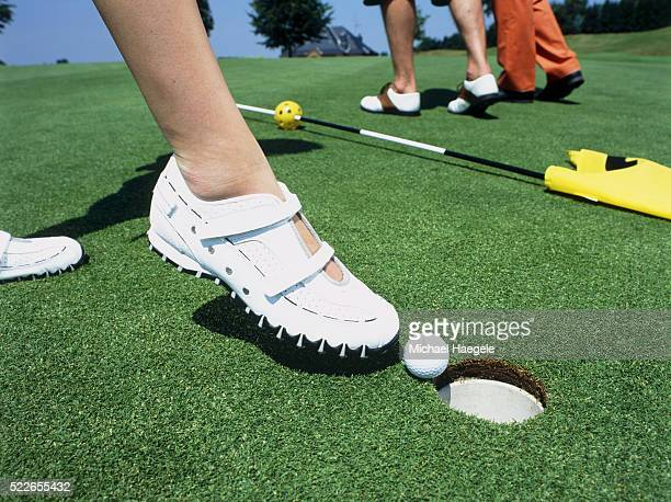 Woman nudging golf ball into hole with foot