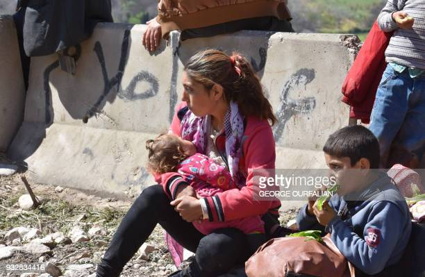 A woman nurses her baby as civilians fleeing the city of Afrin in northern Syria walk at the mountainous road of alAhlam while heading towards the...