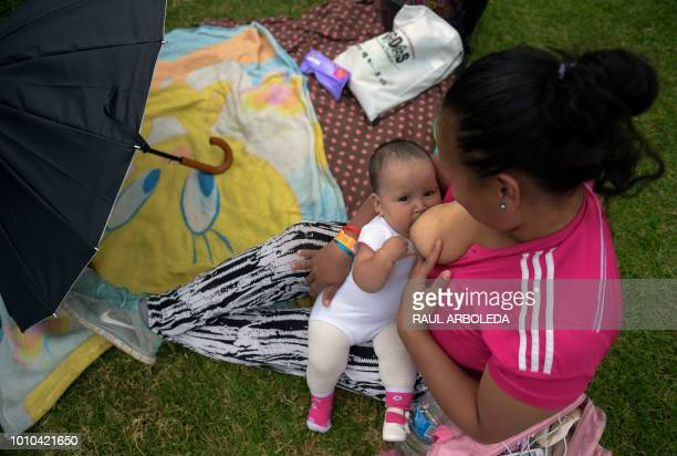 A woman nurses her baby during a public event to promote the benefits of breastfeeding during the World Breastfeeding Week at a park in Bogota on...