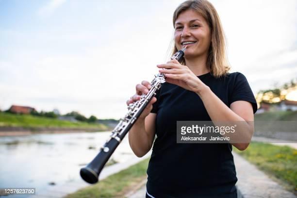 eine oboenspielerin am fluss - oboe stock-fotos und bilder