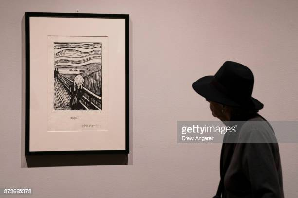 A woman observes a lithographic crayon version of 'The Scream' during a preview of the Edward Munch exhibition titled 'Between The Clock and The Bed'...