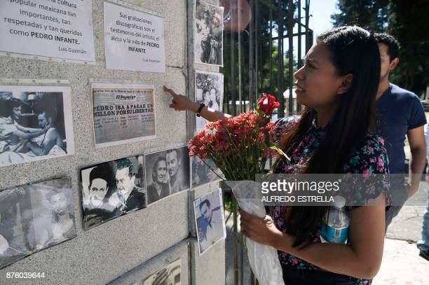 A woman observes pictures of Mexican singer and actor Pedro Infante's during the 100th anniversary of his birth at the Panteon Jardin in Mexico City...