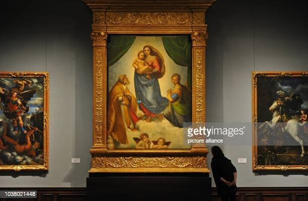 Woman observes Raffael's 'Sistine Madonna' from 1513 at the Gobelin hall of the Gemaeldegalerie Alte Meister in Dresden, Germany, 27 March 2013. The...