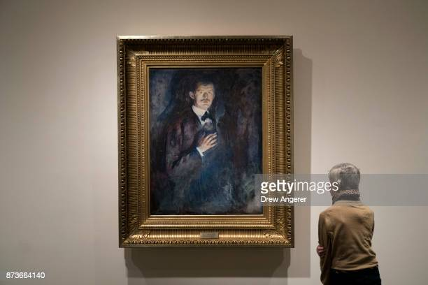 Woman observes 'Self-portrait with Cigarette' painting during a preview of the new Edward Munch exhibition titled 'Between The Clock and The Bed' at...