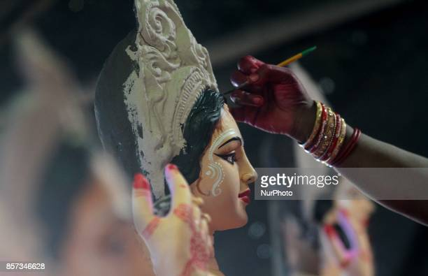A woman of a traditional artistic family applying colors into the idol of wealth goddess Lakshmi ahead of the Lakshmi Puja festival at a village...