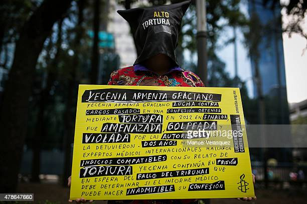 A woman of Amnesty International holds a banner during the protest as part of the UN's International Day in Support of Victims of Torture at Attorney...