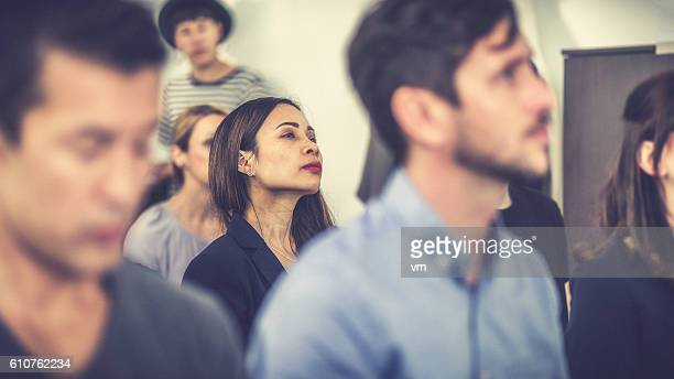 Woman of Asian ethnicity in a seminar audience