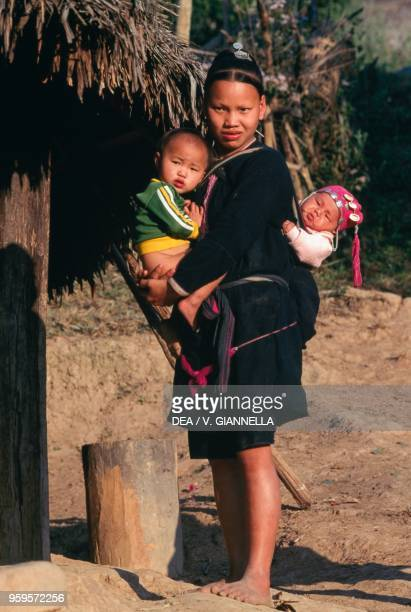 Woman of Lanten people with two children, village of Ban Nam Dee, Laos.