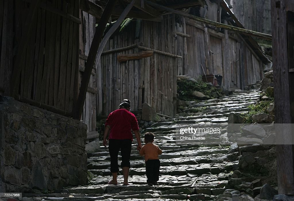 A woman of Miao ethnic origin leading a boy walks at Langdeshang Village on October 21, 2006 in Leishan County of Qiandongnan Miao and Dong Autonomous Prefecture, Guizhou Province, China. With a population of 8,940,116, the Miao people is one of the largest ethnic minorities in southwest China. Qiandongnan Prefecture is a multi-ethnic region where over 20 ethnic minority groups reside. Miao and Dong minorities make up over 70 percent of its population.