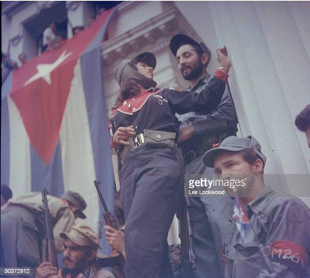 Woman of the 26th of July militia standing guard w fellow rebels during one of Castro's lengthy victory speeches en route to Havana
