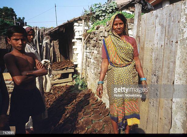 A woman of the Harijan caste stands amid dung patties October 28 1991 in India The Harijan caste is the lowest in the Hindu class hierarchy and its...