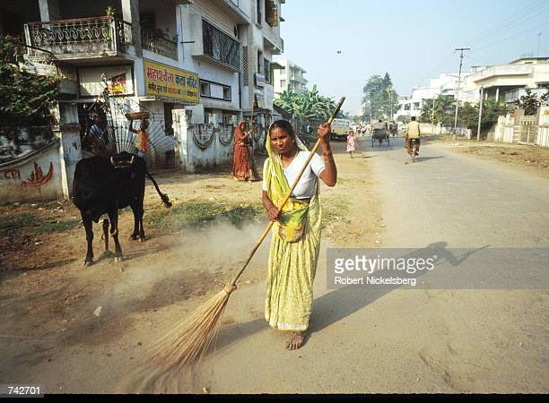 A woman of the Harijan caste sweeps the street October 28 1991 in India The Harijan caste is the lowest in the Hindu class hierarchy and its members...