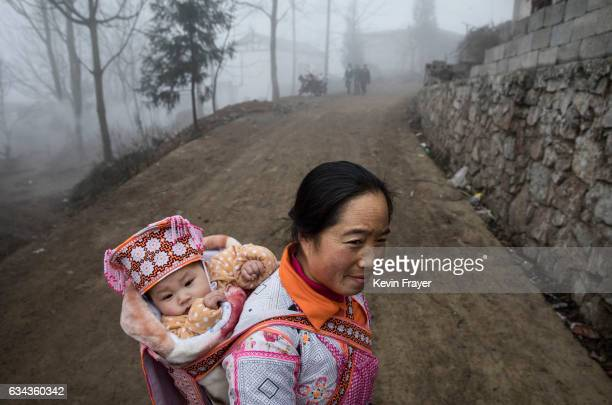 A woman of the Long Horn Miao ethnic minority group carries a baby in traditional clothing before Tiaohua or Flower Festival as part of the Lunar New...