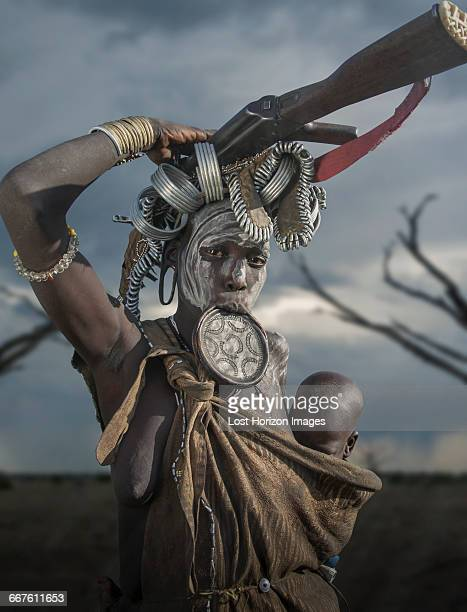 woman of the mursi tribe with kalashnikov and small child, omo valley, ethiopia - lip plate stock photos and pictures