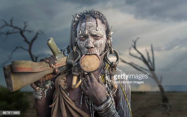 woman of the mursi tribe with kalashnikov gun, omo valley, ethiopia - african tribal culture stock pictures, royalty-free photos & images
